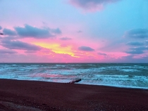 Pink sky by raging waves   before full cloud  and rain  beautiful omen
