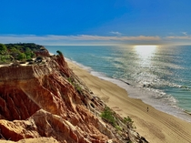 Praia da Falsia Portugal - the distinctive orange red cliffs make for a great contrast against the water