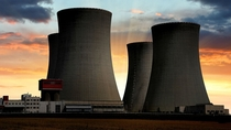Quad hyperbolic cooling towers at a huge electric power plant during a lovely sunset