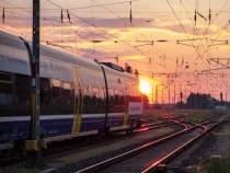 Railroad train amp catenary in sunset