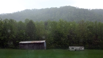Rain falls on a beautiful abandoned barn and trailer out in a field in Cosby TN