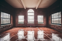 Rain soaked red brick sun room in an abandoned asylum