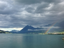 Rainbow on the hills across a lake in Giswil Switzerland