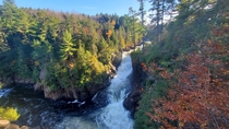 Rapids flowing through a serene autumn forest in Quebec Canada