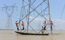 Reinforcing electric pylons at a flooded area in Xuancheng China