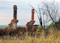 Remains of stoves and pipes on the site of a burned down two-apartment building in the abandoned village of Volosnitsa on the Kama River in Russia