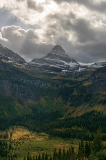 Reynolds mountain peppered with snow cutting through the mid-day clouds Glacier NP Montana
