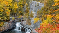 Rich fall foliage gracing the cliffs and waterfalls of Gulf Hagas Maine USA