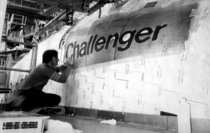 Rockwell International worker painting Challengers name on the starboard side of her forward fuselage just prior to roll-out in