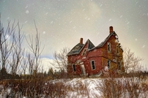 Rural decay of a century farmhouse in a winter snow storm Shelburn Ontario Canada Photo by Ron Clifford