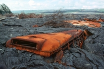 Rusted remains of a school bus eaten by lava in Kalapana Hawaii photographer unknown