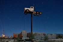 s vintage kenworth mounted atop a pole at an abandoned truck repair yard along interstate   old route  By eyetwist