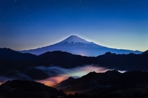 Sacred Mountain - Mount Fuji among clouds lit up by lights below  by Yuga Kurita x-post rJapanPics