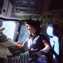 Sally Ride the first American woman in space looks out the window of the Space Shuttle Challenger in