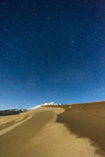 Sand and snow capped mountains under the stars at Great Sand Dunes National Park Colorado