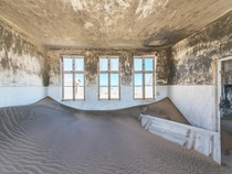 Sand devours a building in the abandoned diamond-mining town of Pomona on the Namibian coast