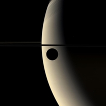 Saturn and its moon Rhea photographed in color a few years ago by the CassiniHuygens probe At right the shadows cast by Saturns rings are clearly visible  photo credit Cassini Imaging Team NASA