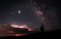 Saturn Jupiter and the Milky Way in the sky and a thunderstorm on the distant horizon seen atop Dolly Sods West Virginia