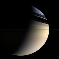 Saturns rings are viewed edge-on by Cassini with the rings shadows cast against Saturns clouds Ice moon Enceladus makes a cameo