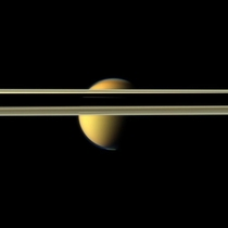 Saturns rings obscure part of Titans colorful visage in this image from NASAs Cassini spacecraft The south polar vortex that first appeared in Titans atmosphere in  is visible at the bottom of this view