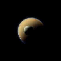 Saturns two largest moons Titan and Rhea appear stacked on each other in a true-color image from Cassini