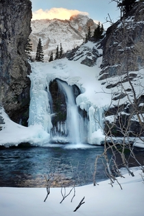 Saw cougar tracks in the snow on the way to this half frozen waterfall Just another day in the Rocky Mountains of Alberta