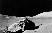 Scientist-astronaut Harrison H Schmitt standing next to a huge split lunar boulder during the third Apollo  extravehicular activity