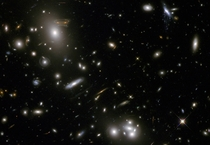 Second image of the Hubble Telescope Advent Calender deep field shows gravitational lensing of massive galactic cluster Abell  magnifying brightening and distorting distant galaxies behind it