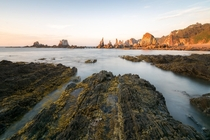 Sharp rock formations emerge during low tide in Gueira Asturias Spain