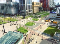 Side walk dedicated cycle paths tram tracks motor way in front of train station square Rotterdam the Netherlands