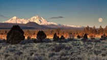Sister mountains with the full moon setting at sunrise west of Bend Oregon