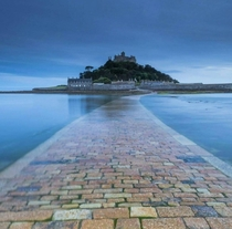 Slightly submerged yellow brick road to St Michaels Mount Cornwall UK