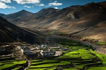 Small farming village cut into the Tibetan landscape