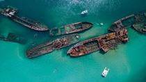 Small speed boats explore the turquoise waters that house a ship graveyard full of yesteryears vessels TANGALOOMA AUSTRALIA