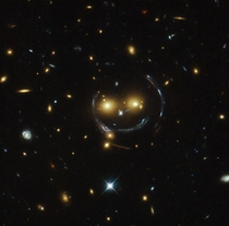 Smiley face in space this is a phenomena known as gravitational lensing Its where gravity is so strong from a distant object that it warps the spacetime around a body in between Earth and the massive body