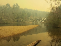 Smoke from a wildfire filtering the light at Rocky Falls Missouri