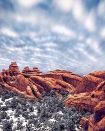 Snow at Arches NP - Moving clouds above mimic the lines and shapes of the red rocks below