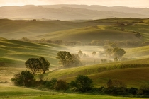 Soft light over the foggy valley of Val dOrcia Tuscany Italy  Photo by Tobias Richter