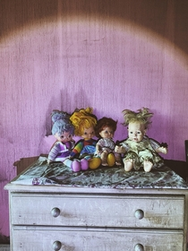 Some dolls watching over a girls abandoned bedroom