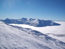 Southern Alps NZ poking up above the clouds  Photo taken from Treble Cone Skifield