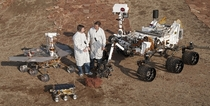 Spacecraft engineers stand with three generations of Mars rovers JPLs Mars Yard testing area