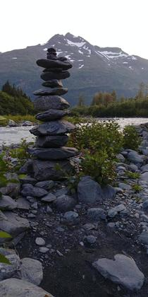 Stack of stones in the foreground of an unnamed mountain found while hiking along a glacier stream near Whittier Alaska