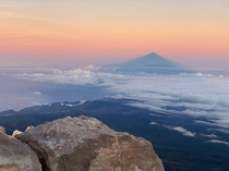 Standing on the m summit of Teide the highest point in Tenerife watching the rising sun cast a shadow over the island of La Palma over km away