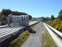 Steam pipelines leading from a steamfield near Lake Taupo to the geothermal power plant at Wairakei Region of Waikato New Zealand