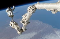 Stephen K Robinson anchored to a foot restraint on the International Space Stations Canadarm participates in the missions third session of extravehicular activity August