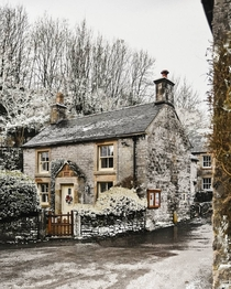 Stone cottage in snowy Milldale Peak District Derbyshire England