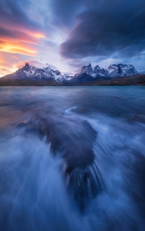 Stormy lakeside view with glowing lenticular clouds at sunset Torres del Paine NP Chile