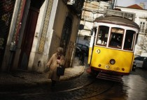 Street scene A woman walks near a tram at the Alfama neighborhood in Lisbon Portugal
