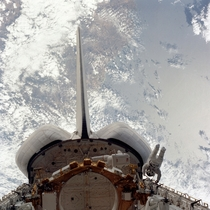 STS- mission specialists Donald H Peterson on the right side of the picture and Story Musgrave back to camera inside the cargo bay evaluate the handrail system on the Space Shuttle Challenger during an EVA