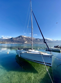 stunning midday shot of the crystal clear Lake Annecy tucked away in Eastern France